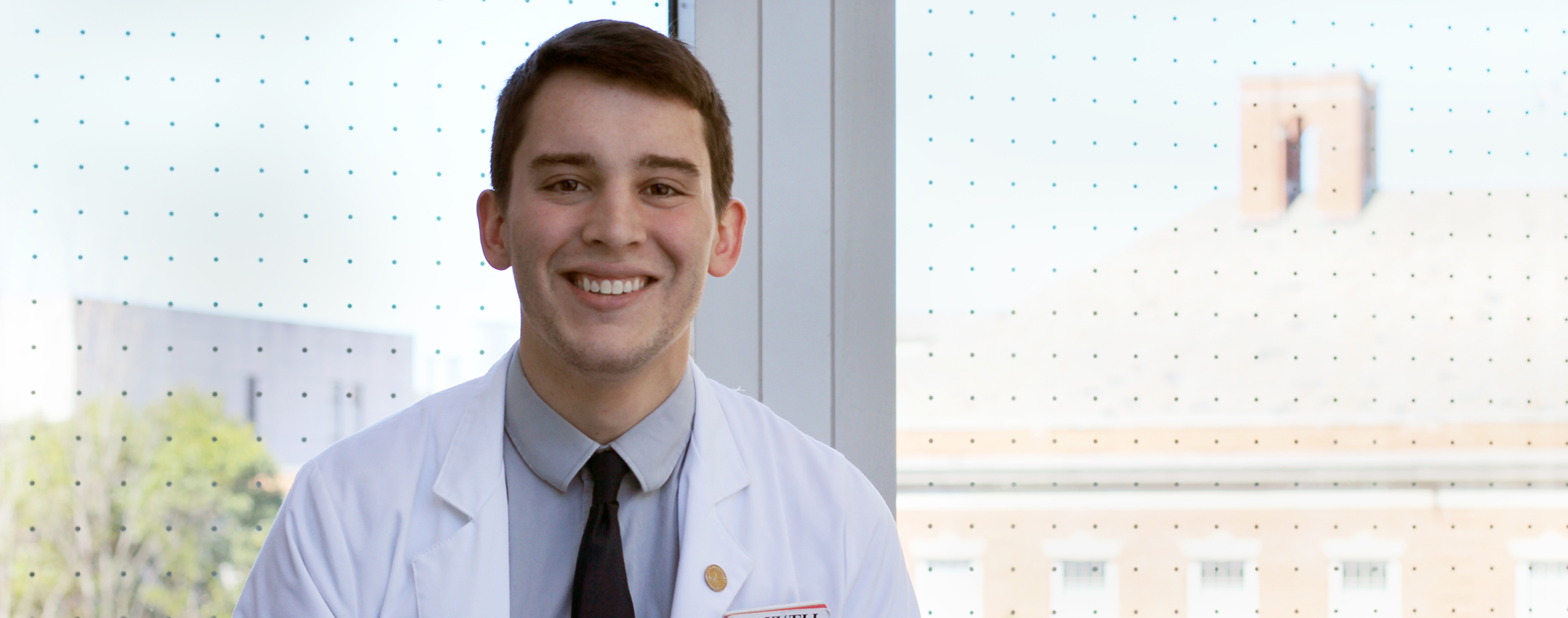 Duke MD-MEng student Joshua D'Arcy in a white coat
