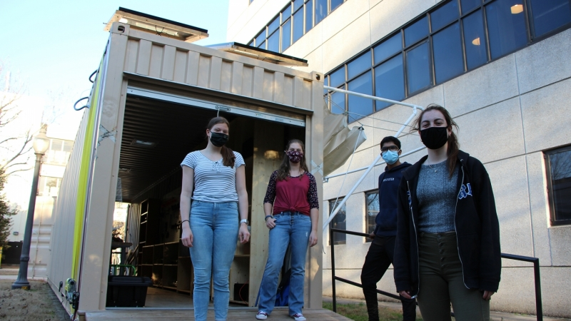 student team in front of shipping container makerspace