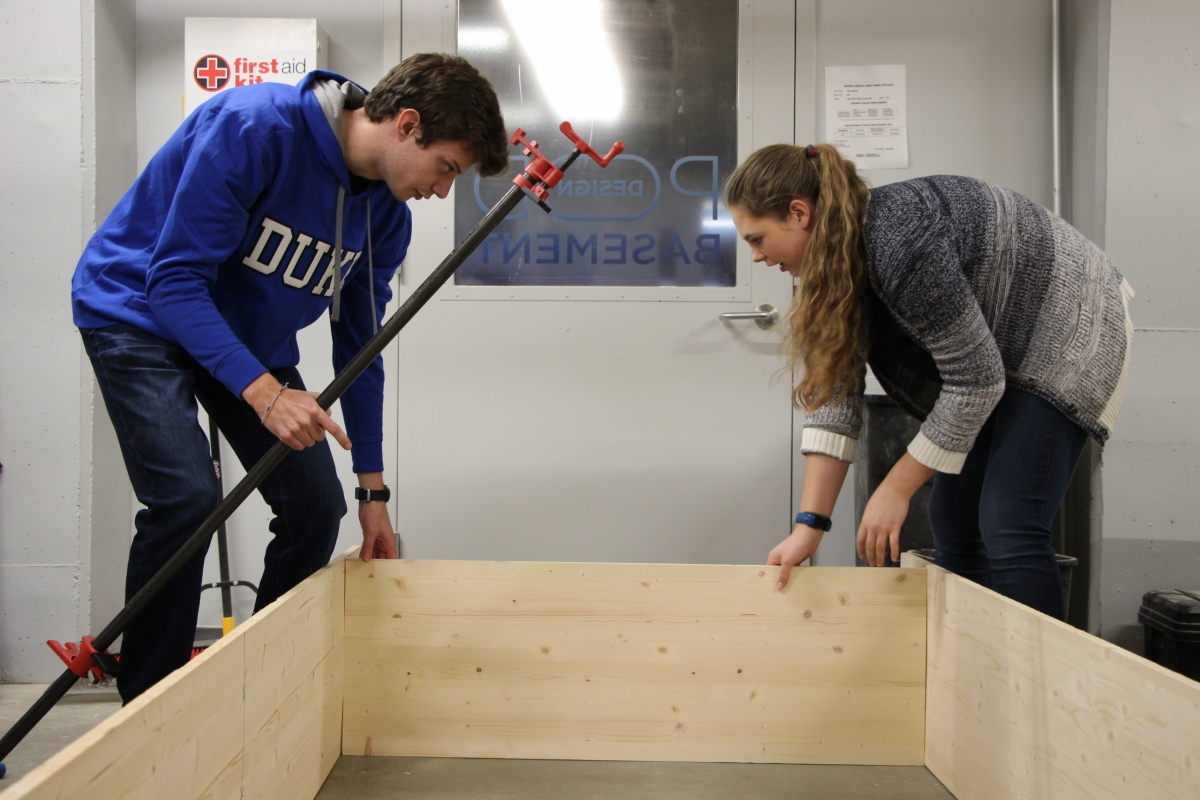 Students begin assembling a bookshelf to be placed in the shipping container