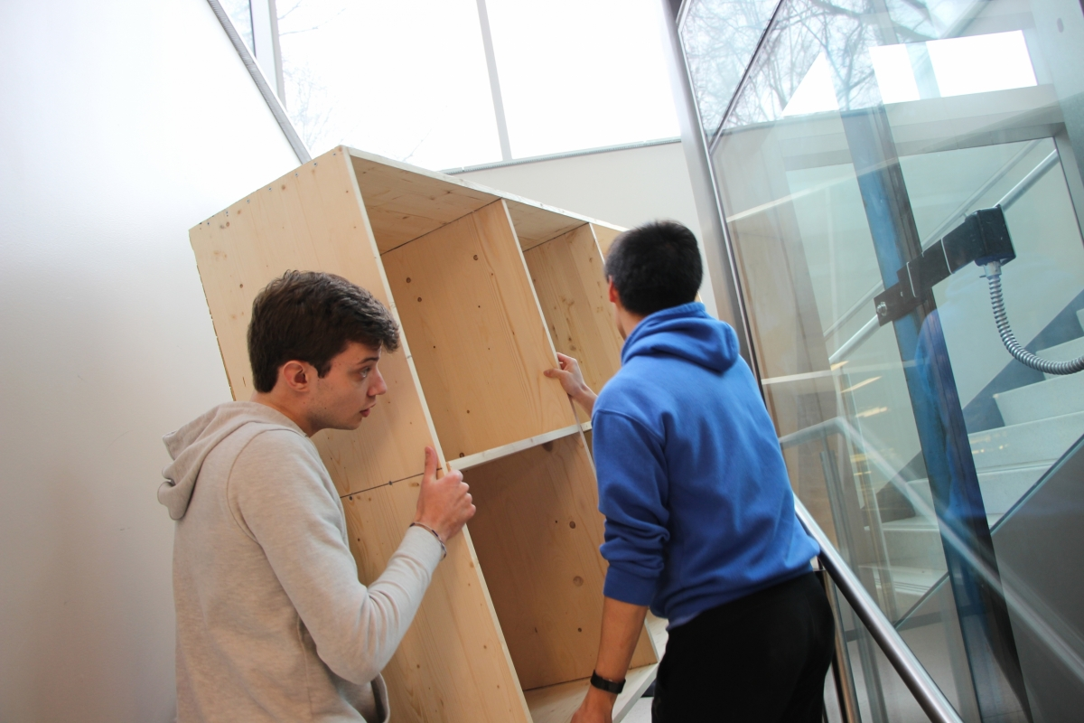 The team moves the bookshelf from their workspace
