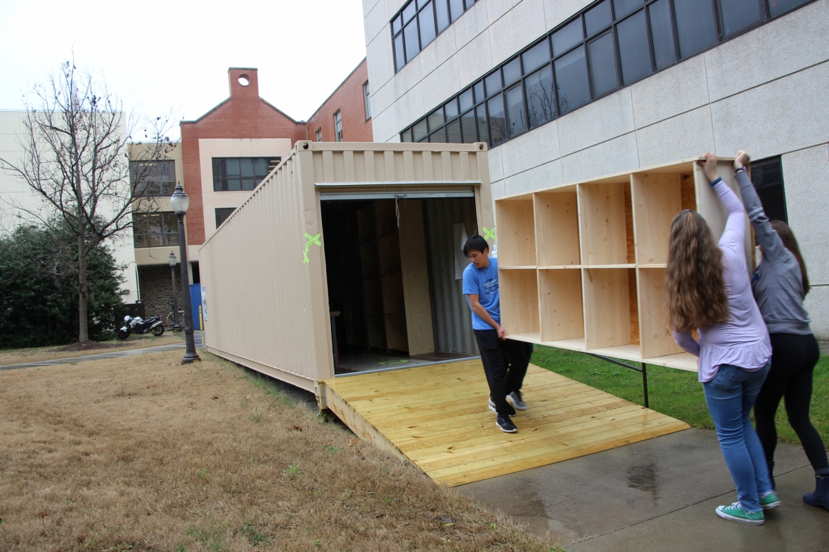 The team brings the bookshelf to the storage container