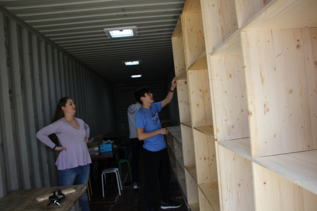 The students secure the placement of the new bookshelf