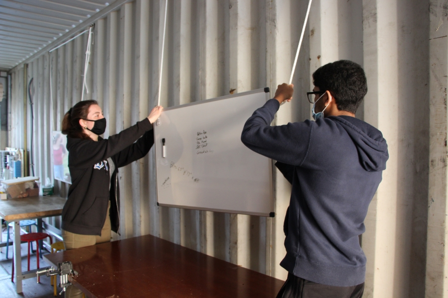 Students hang up a white board in the container